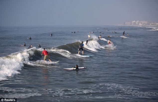 Surf's up: People surf on Friday at Rockaway Beach in New York
