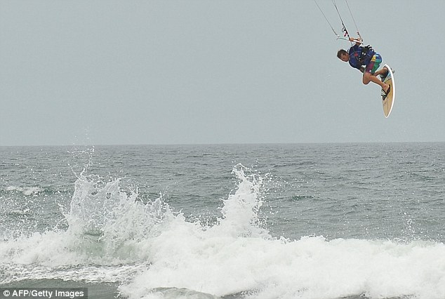 In the air: A man is seen parachute surfing at the beach in Kill Devil Hills in the North Carolina Outerbanks on Friday ahead of the expected landfall in the area of Hurricane Irene