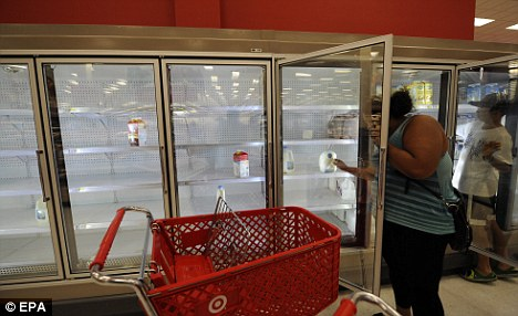 Cleaned out: Milk refrigerators sit almost empty at a Target store as New Yorkers stock up on supplies in preparation for Hurricane Irene in Queens