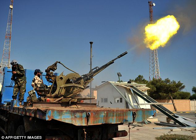A rebel celebrates by shooting an anti-aircraft gun in Ras Jdir, west Libya after capturing the border town