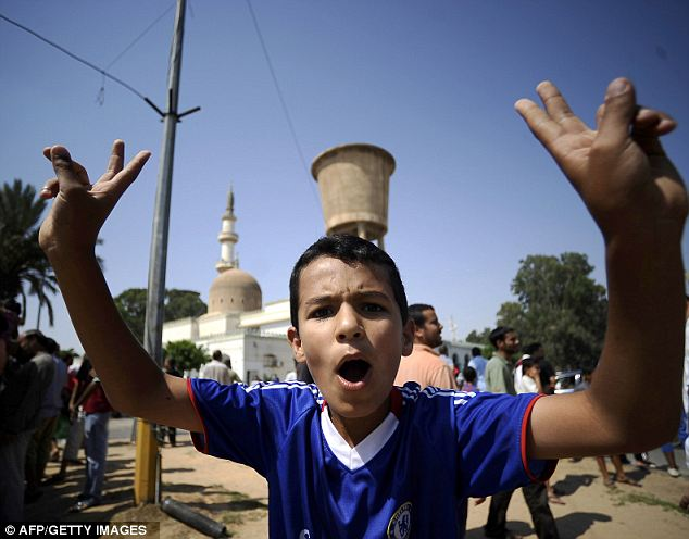 A young boy flashes the V-sign for victory as rebels celebrate after a south-western neighbourhood of Tripoli was taken over by rebel forces