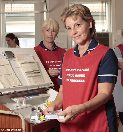 Bitter pill to follow: Ward manager Penny Searle wears the controversial tabard during a drug round