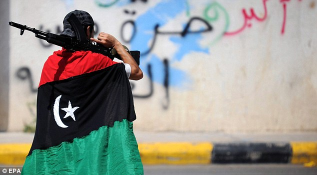 Clash: A Libyan man is wrapped in the rebel's flag as he holds a gun at a checkpoint, in Tripoli today. Fighting continued in Sirte
