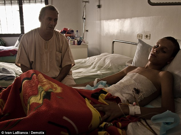 Victim of war: Thirteen-year-old Msalem Bashir's father sits beside him at Tripoli's Cental Hospital. The boy was injured while playing with a large caliber bullet