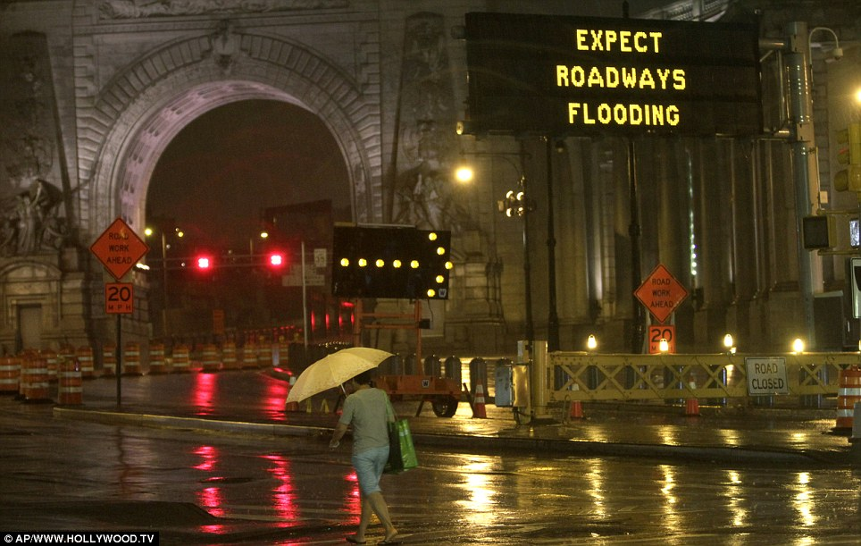Words of warning: A pedestrian takes a risk as roads are closed and barricades raised in Lower Manhattan with Hurricane Irene expected to bear down on the city today