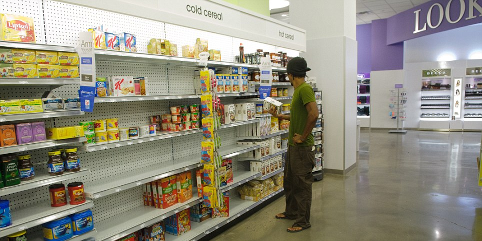Slim pickings: A shopper makes the most of the cereals on offer as milk and bread supplies ran out in New York stores