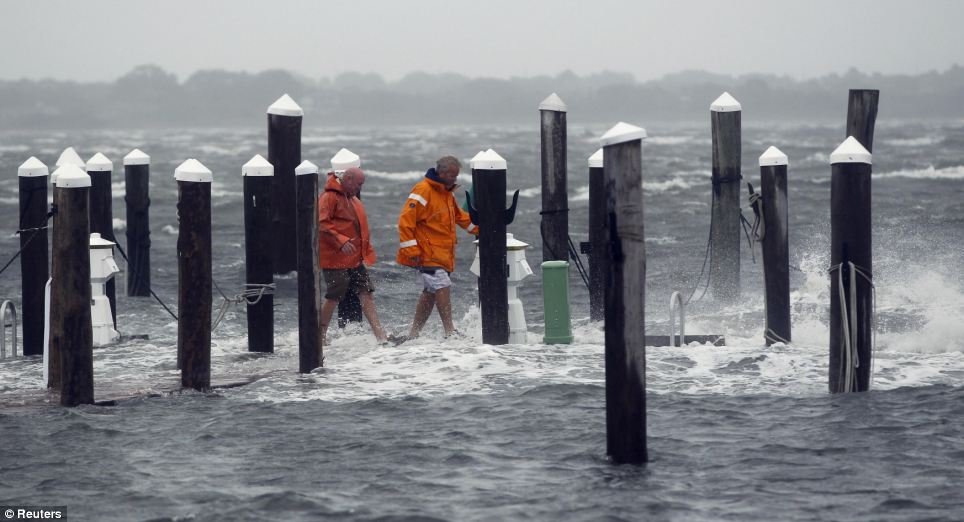 Wading: Captain Jon Jedlicka, right, and John Murray check storm damage along a dock as it is battered by the storm surge and winds from Hurricane Irene in Montauk, New York
