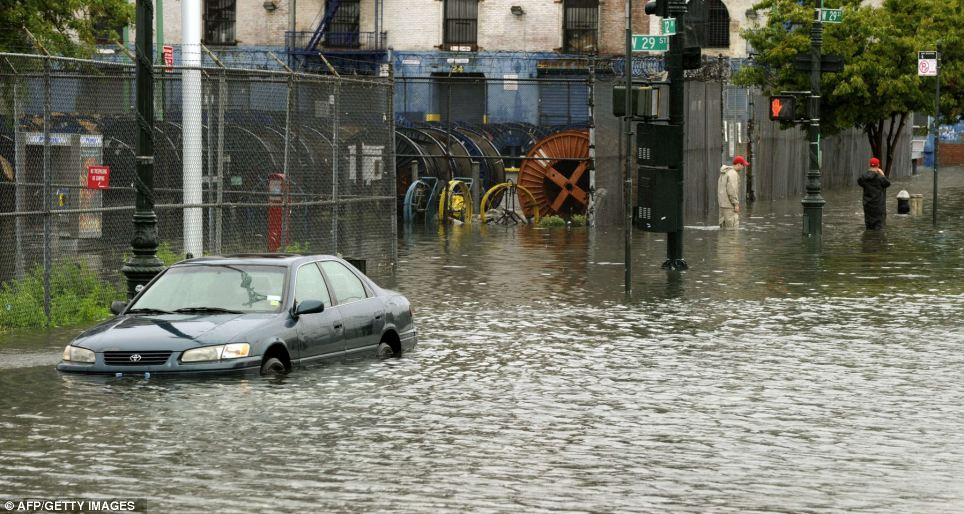 Some damage: People wade through the water on a flooded section of 12th Avenue in New York today