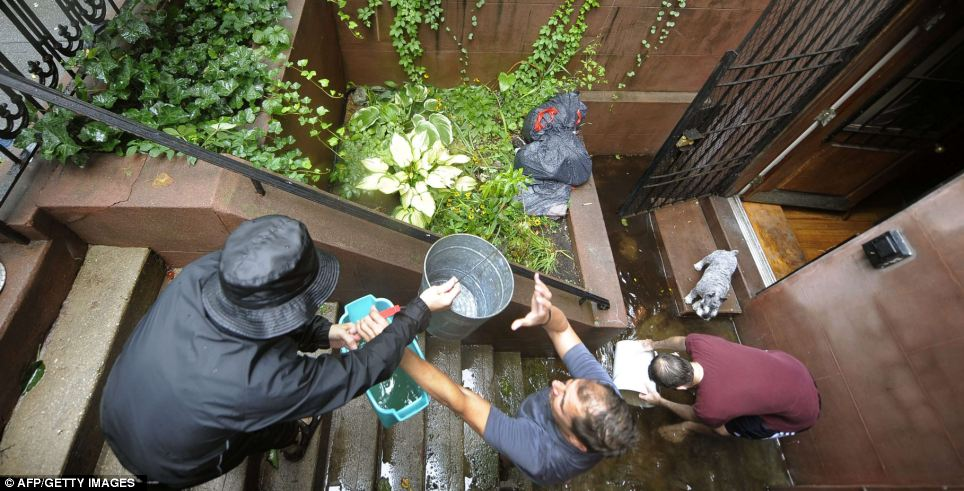 Community spirit: People pitch in to help clear the flooded apartment in Chelsea, Manhattan