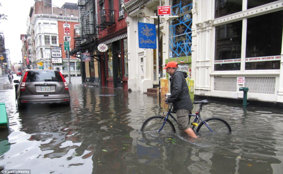 Not going anywhere fast: A man tried to ride his bicycle through flood water in lower Manhattan this morning