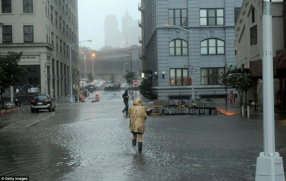 Soaked: A Brooklyn resident wades through flood waters filling the intersection of Main St and Plymouth St