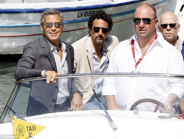 Riding in style: Clooney and screenwriter Grant Heslov (centre) took a water taxi to the press conference