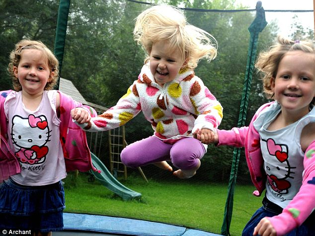 Full of energy: Megan, left, and Gracie, right, are seen here playing with their little sister Martha