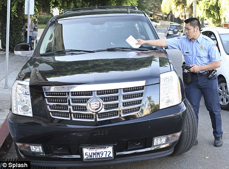 Red zone: Lindsay's huge Cadillac Escalade gets slapped with a ticket that will cost her about $70