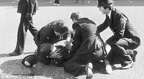Tragic: Officers attempt first aid on WPC Yvonne Fletcher as she lies wounded on the pavement