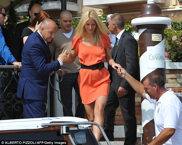 Helping hand: Gwyneth is helped down some steps in front of Matt Damon, her co-star in the gripping virus disaster film