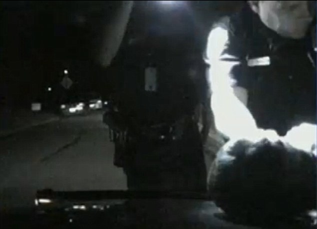 Combative: Hamm's head is seen on the hood of a police cruiser after he refuses to obey the orders of officers
