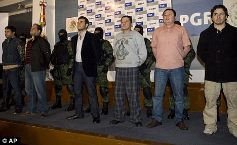 Rounded up: Vicente Zambada, third on the left, and five others are paraded before the media after their capture in 2009