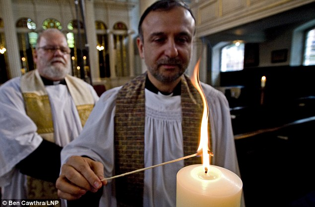 Flame of hope:  Fathers James Roesthal, left and Natim Nassar  light a candle at Grosvenor Chapel near the U.S Embassy yesterday