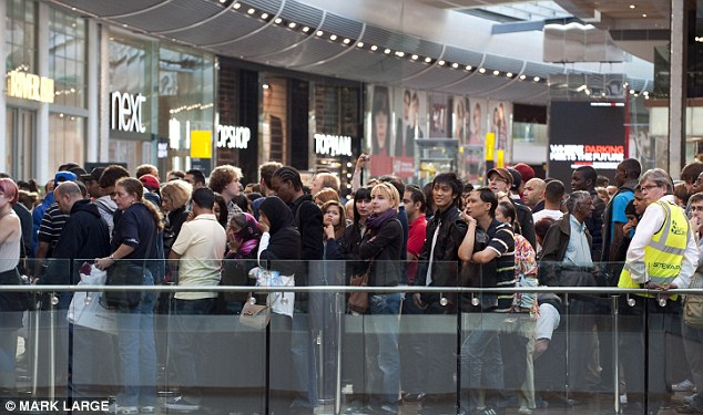 Waiting patiently: Hordes queue to be allowed entry into the shopping centre ahead of the first day trading