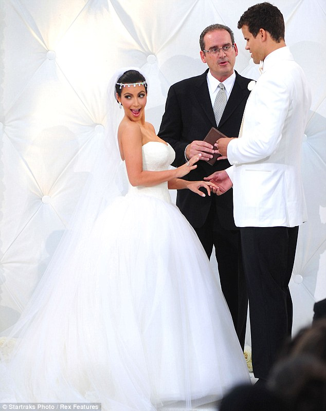The big moment: Kim smiles at her sisters as she exchanges rings with Kris at twenty past seven in the evening on August 20
