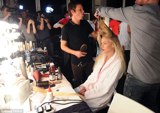 Coiffed: A model is tended to by two stylists, sitting at a desk strewn with fashion week essentials - gallons of hairspray, make up and bottles of glaceau vitaminwater to revive flagging energy levels