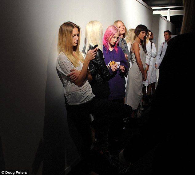 Waiting game: Models kill time before getting hair and make up ready for the show