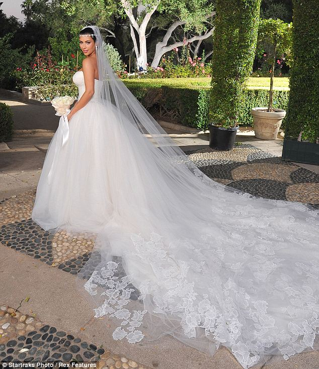Fairytale princess: Kim poses with her incredible dress in the dramatically lit grounds of the private estate where the wedding was held