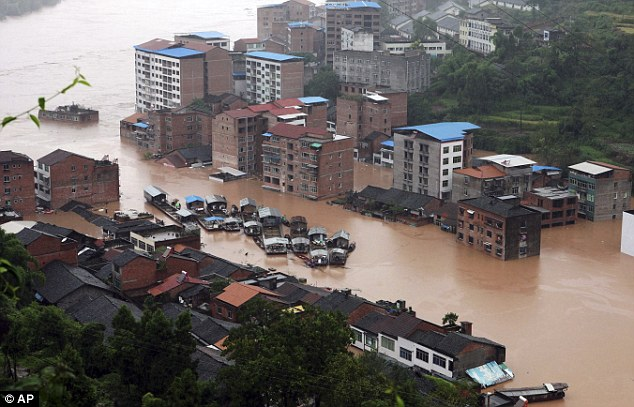 Wash out: In this photo taken on Monday, boats are gathered in the midst of a flooded section of the town in Daxian county in southwest China's Sichuan province