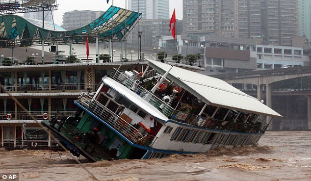 Struck: The passenger boat capsizes after being hit by a restaurant boat on the flooded Jialing River in southwest China's Chongqing municipality