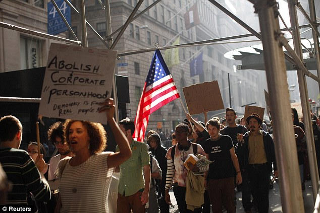 Public anger: Protesters demonstrate outside the New York Stock Exchange on Wednesday on the fourth day of protests as they call for action against big businesses and politics