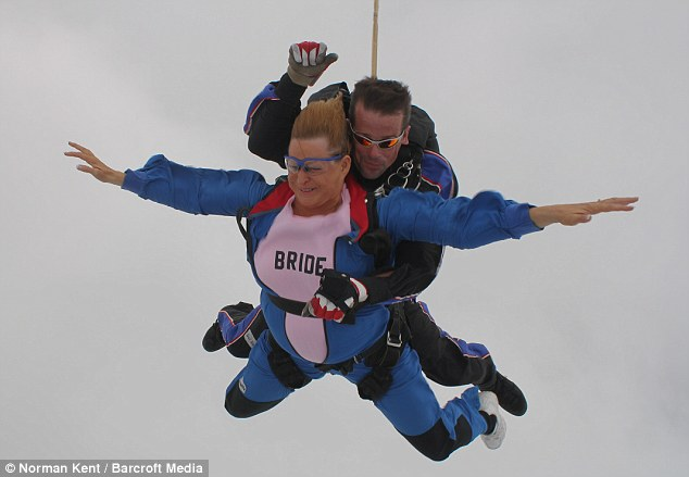 Taking the plunge: Gail Mathis during her wedding skydive, she jumped out of the plane alongside her new husband, but was attached to an experienced skydiver in the tandem leap