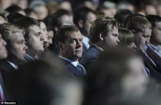 Dmitry Medvedev sits among party members after ending speculation about whether he would run for another term