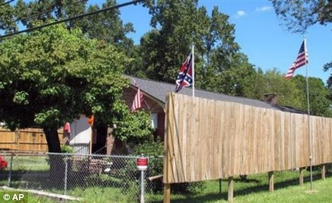 Flag war: Ms Caddell put up a new flag pole this summer that can be seen over the fence