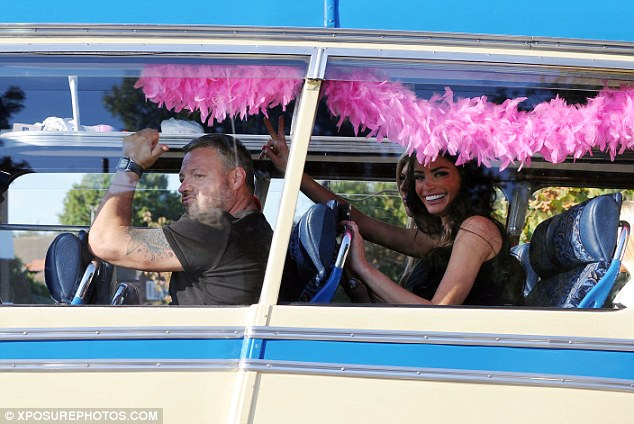 All aboard! Mick, Chloe and Frankie lark about as they take their seats on the blue and cream bus which was decorated with pink boas