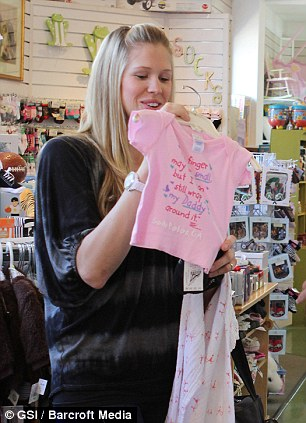 Happy new mom: Victoria appears to be a natural as she cuddled her little girl and looked at pink clothing