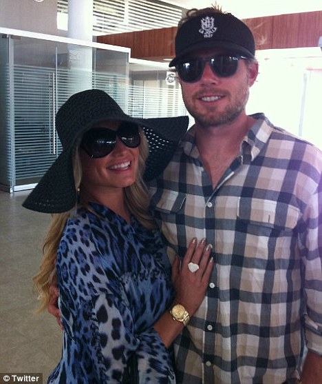 Happy holidays: Jessica, in yet another cover up, poses with Eric as they prepare to fly back to LA