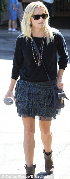 Spring in her step: Reese, meanwhile, opted for a short tired skirt and and a black top