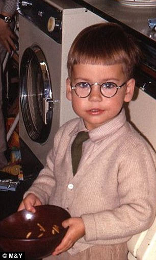 In a spin: Doug as a child pictured in the kitchen of his childhood home with the tumble dryer that has been going strong for more than 50 years