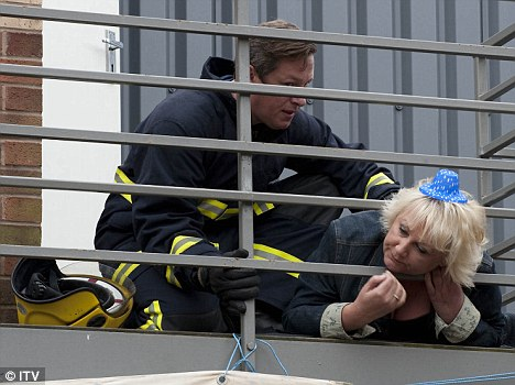 To the rescue: Corrie's Eileen Grimshaw is saved by fireman Paul after she gets her head stuck in Underworld's roof railings on her 50th birthday