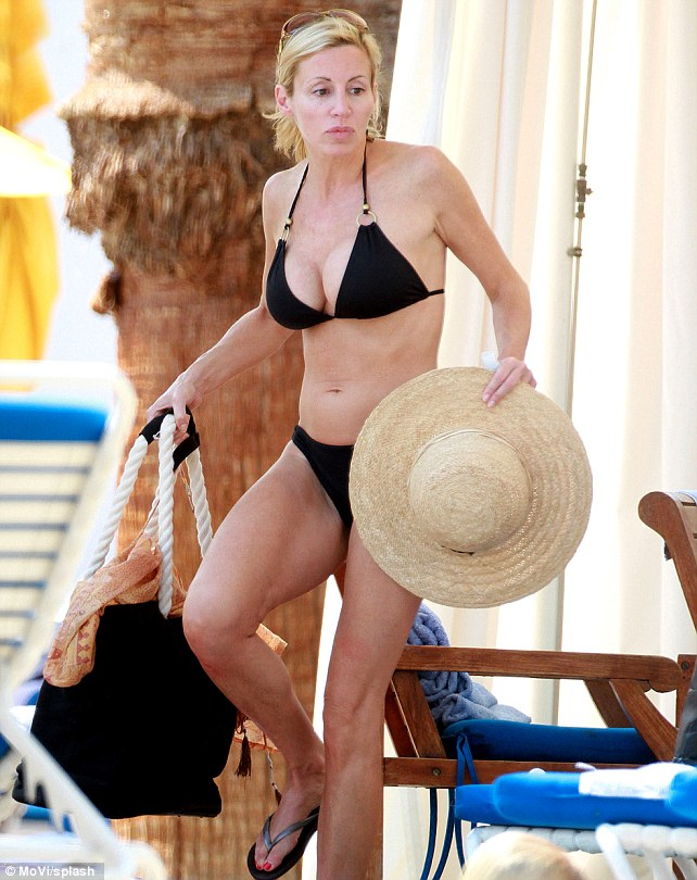 Poolside chic: Make-up free and her blonde hair pulled back in a pony tail, the reality star looked confident as she lounged poolside in the designer two-piece