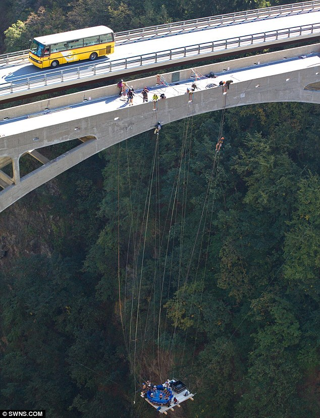 Taking the plunge: Daredevils dangled 500ft from the ground and 120ft from the bridge as they took part in an 'extreme jacuzzi' stunt