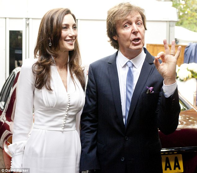 Showing off: Sir Paul McCartney showed off his gold wedding band as he and Nancy headed into the marquee at their London home
