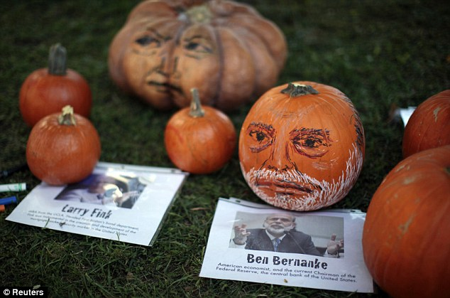 Halloween theme: Pumpkins with the faces of bankers are displayed at the Occupy LA camp on Sunday