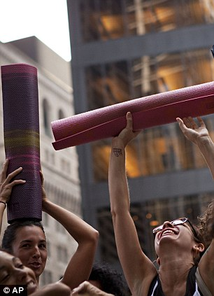 Yoga: Women who came to practice yoga in participation with the Occupy Wall Street protests lift their yoga mats in the air while listening to yoga instructor Seane Corn speak in Zuccotti Park in New York