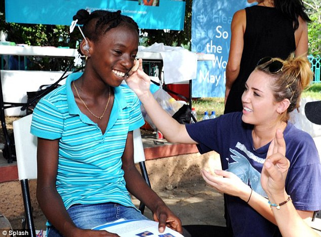 Hear no evil: Part of Miley's job  in Haiti was to fit children with hearing aids