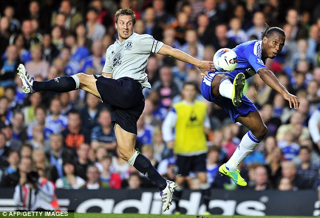 Foot loose: Jagielka (left) and Drogba contest a high ball