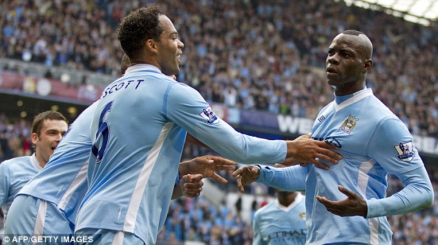 Cheer up, Mario: Balotelli is mobbed by Lescott and Kompany after scoring City's first goal against Aston Villa