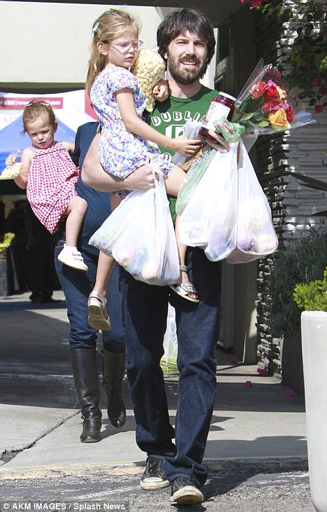 At the helm: Ben carried both the groceries and his oldest daughter Violet as the family made their way around the stalls