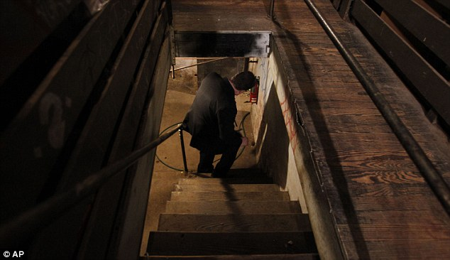 Grim discovery: Sgt. Joseph Green walks down the steps leading to the sub-basement where four weak and malnourished adults, one chained to a boiler, were found at the weekend
